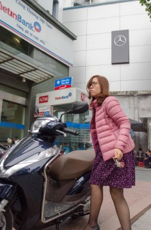 Woman Locks Helmet in Front of Bank
