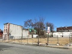 Fenced vacant lot and vacant rowhouse following emergency demolition, 1214-1228 Hollins Street, Baltimore, MD 21223