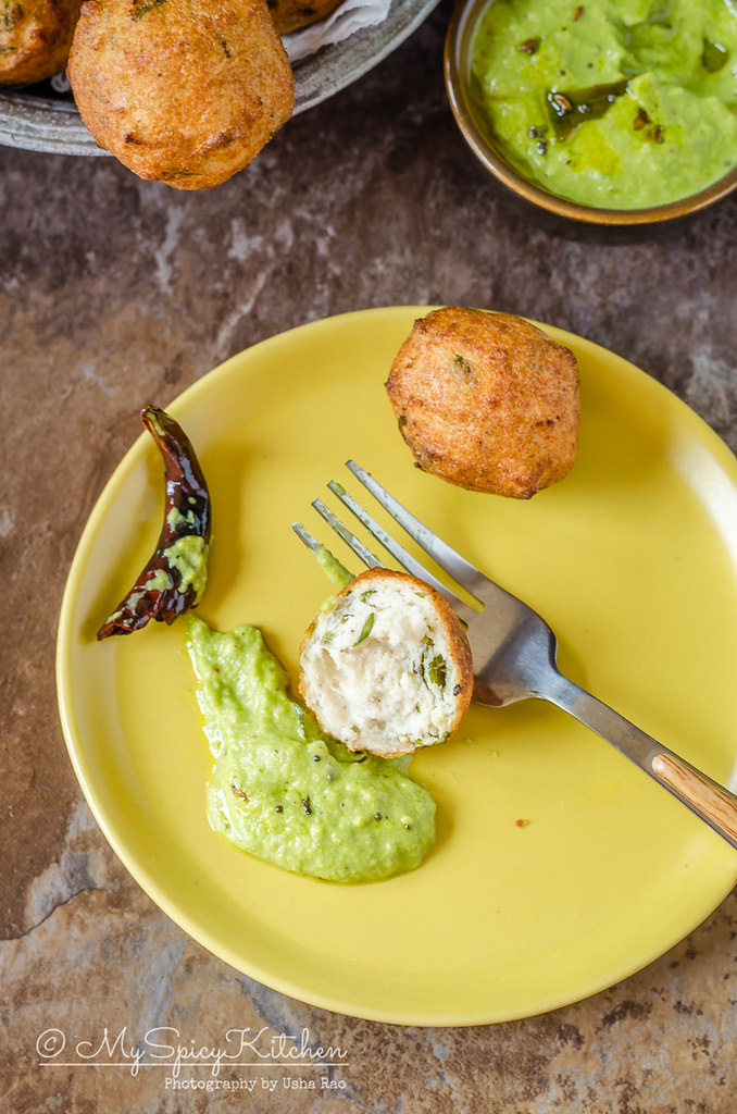 A plate of urad dal bonda with coconut chutney.  Urad dal bonda is a crispy deep fried snack made with urad dal.