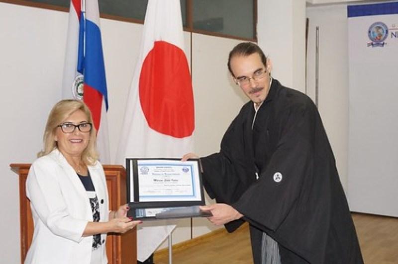 Recibo un diploma y una insignia del Nihon Gakko de manos de su vicerrectora.