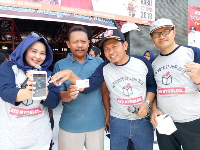 Komisioner KPU Tulungagung memandu warga untuk mengecek DPS dari handphone saat sosialisasi, Minggu (1/4)