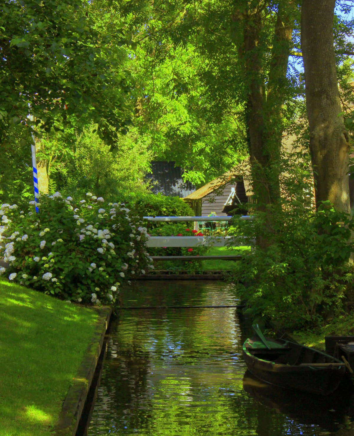 The canals of Giethoorn are shaded by trees.