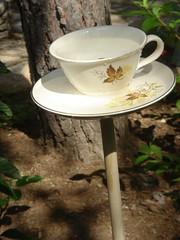 tea cup bird bath in garden
