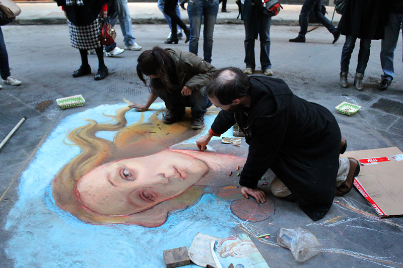 A street artist and his assistant recreate Boticelli's Venus
