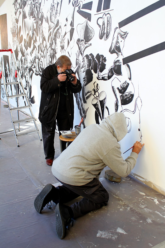 Lucio Pozzi, the artist, welcomes people to take photos of him working on a huge painting