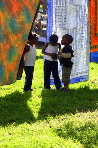 CHILDREN PLAYING IN THE BATIKS AT THE MARKET