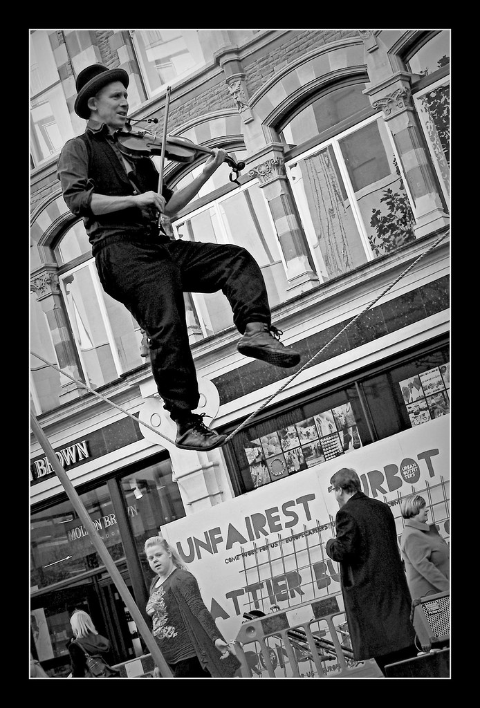 Man playing violin on tightrope in The Hayes