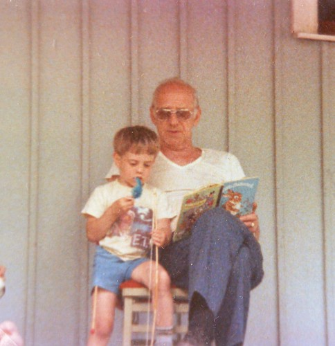 A blond white boy and an older, balding man are reading a children's book on a porch