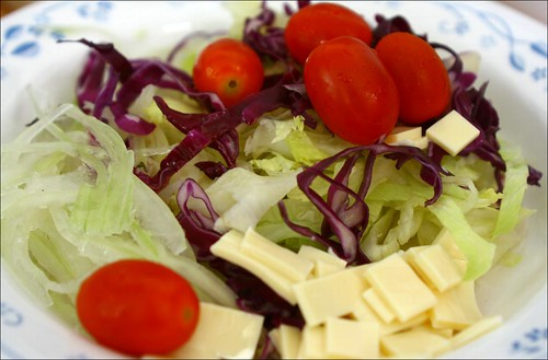 homemade salad with onions, cheese, lettuce, cabbage and tomatoes