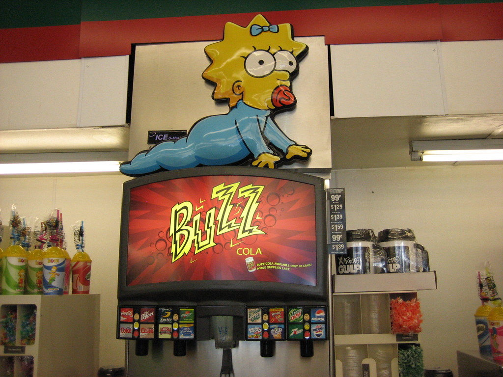 Maggie Simpsons up to the soda machine at kwik e mart