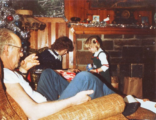 In the foreground in gold-colored recliner is an older white man with glasses, in the background is a brown-haired white woman and a blond-haired little girl