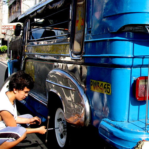 man repairing a jeepney's wheels