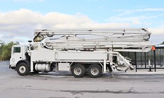 A very white concrete pumping truck