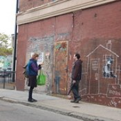 Banksy in Boston: Visitors getting photos with the NO LOITRIN piece on Essex St in Central Square, Cambridge.