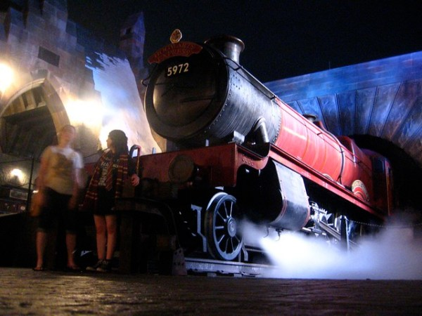 Hogwarts Express billows steam at night in the Wizarding World of Harry Potter