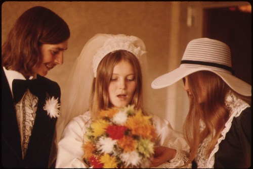 The Bride and Groom and a Member of the Wedding Party with a Bouquet at New Ulm, Minnesota...