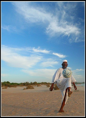 A man playing with a soccer ball in Egypt on a sandy beach.