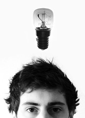 top half of a young man's head with a lightbulb suspended above it