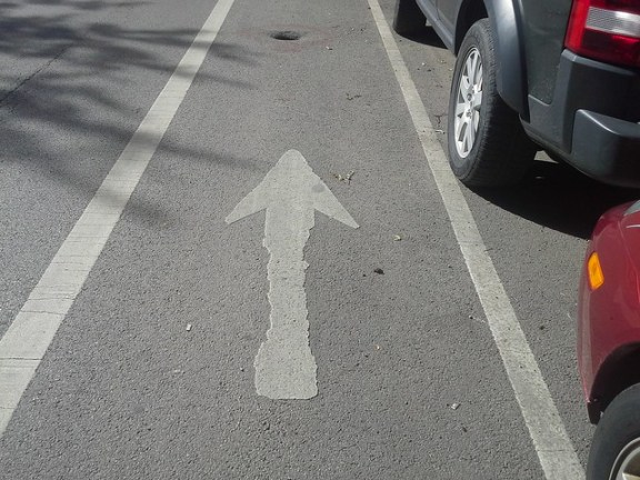 Perspective of bike lane with hole and arrow leading right to it
