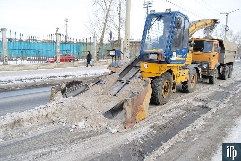 Технология уборки улиц традиционная: лаповый снегопогрузчик загружает самосвал