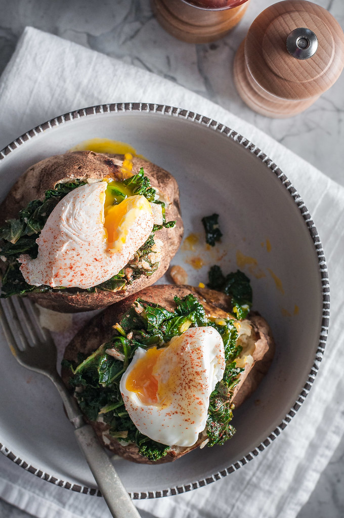 Baked potatoes for breakfast with sauteed parmesan kale and a poached egg