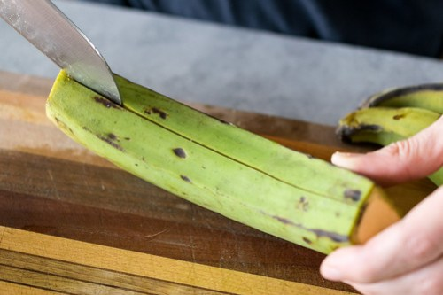 slicing through the thick skin of the plantains