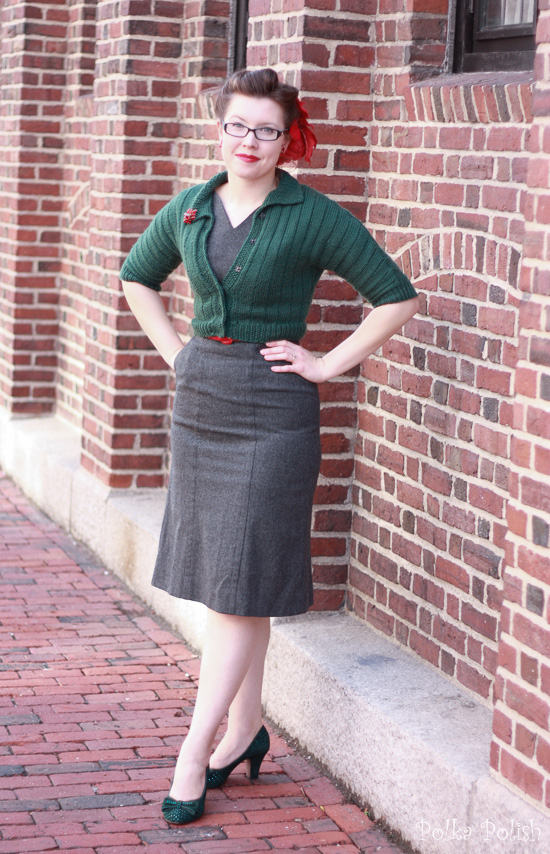 Festive vintage holiday outfit with enormous faux poinsettia, red jewelry, grey dress, green sweater, and green miss l fire gabrielle pumps
