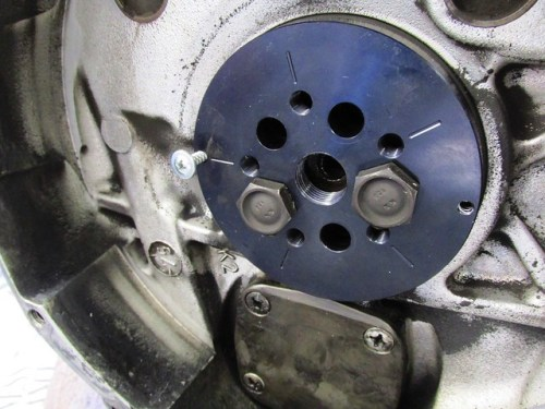 Aligning Puller with Two Flywheel Bolts and Inserting Screw Into Seal