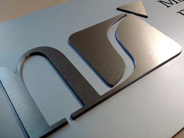 Szyld z aluminium, tło matowe, naklejone litery, grawerowany tekst z emalia