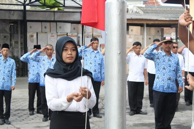 Petugas pengibar bendera mengibarkan sang saka merah putih saat upacara bendera memperingati HUT RI ke-73 di halaman Kantor KPU Tulungagung, Jumat (17/8)