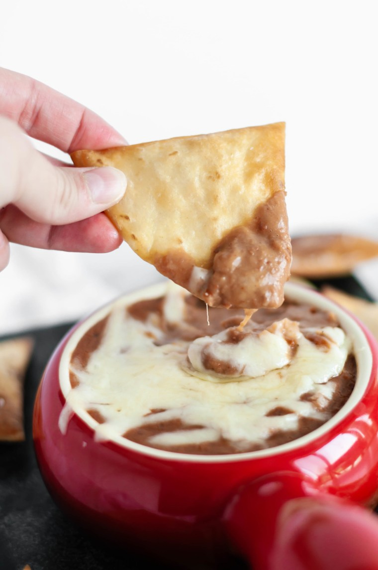 Slow Cooker Cheesy Bean Dip is the perfect addition to your football watch party. 4 ingredients mixed in your slow cooker, a few hours and you're ready for snacking. Homemade flour tortilla chips up your game.