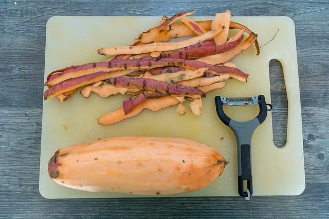 Peeled Sweetpotato with peeler and skin on cutting board