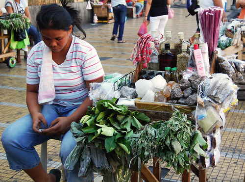 herbal medicine street sidewalk vendor woman texting, cellphone  Buhay Pinoy Philippines Filipino Pilipino  people pictures photos life Philippinen  菲律宾  菲律賓  필리핀(공화�)