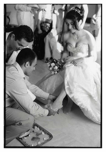 groom putting a shoe on bride's foot