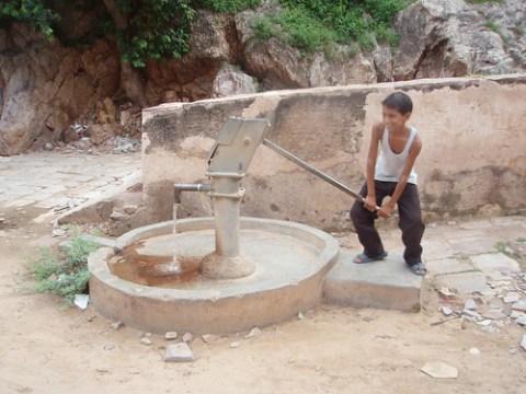 Niño en la India sacando agua del pozo