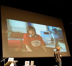 Article image: Mike Rodway speaks to a video of himself on stage.