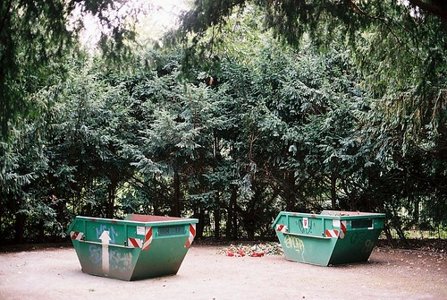 Photo of two trash containers in shady glade.