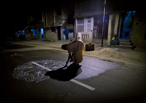 Woman drawing Kolam கோலம்  on the road - India