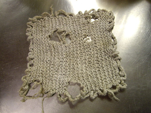 A handknit dishcloth, ragged with age and grey in colour