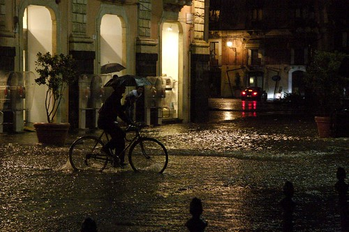 Cyclist with umbrella riding along a flooded street