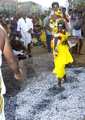 Hindu woman walking on burning coals with her son on the shoulder at firewalking ceremony, Tamil Nadu - India