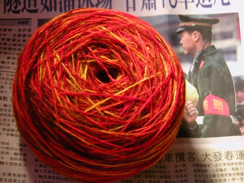 A photo of the finished dyed yarn cake sitting on a Chinese newspaper.  Lookin' good.