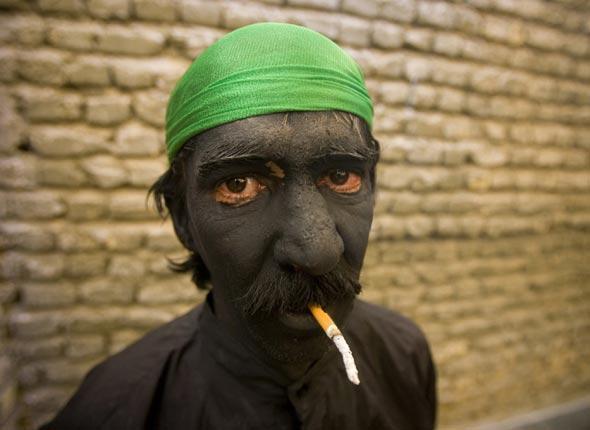 Un participant au carnaval religieux organisé dans le cadre de l'Achoura fait une pause cigarette, Iran, le 17 janvier 2008
