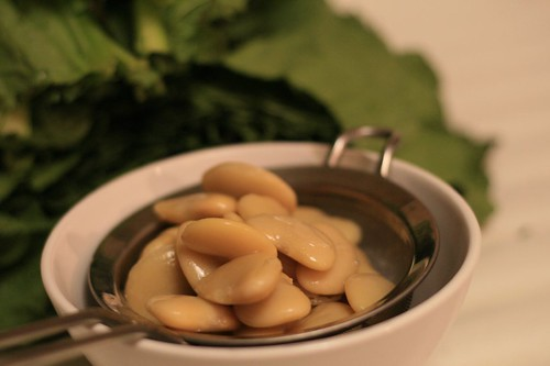 Butter beans draining in front of mustard greens