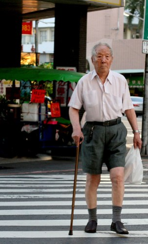 old man in shorts crossing the street with a cane