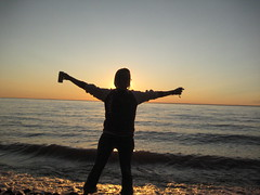 A girl stands with wide open arms gazing at a sunset on Lake Superior