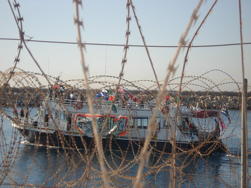 Looking through barbed wire as SPIRIT leaves the mouth of the port by freegazaorg.