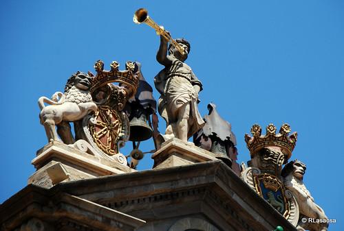 Detalle de la fachada del Ayuntamiento de Pamplona.  Alegoría de la fama con trompeta, de estilo neoclásico, flanqueada por dos leones que sujetan los escudos de Pamplona y Navarra