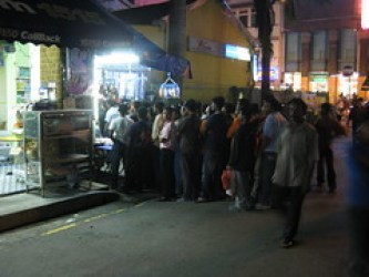 Dozens of local men stand outside a little store watching telenovellas