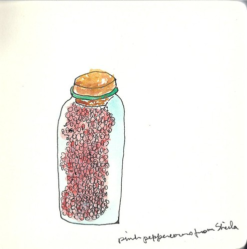 Pink peppercorns in a green glass bottle